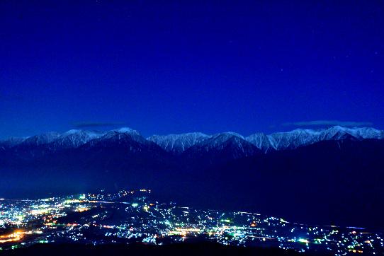 伊那谷の夜景と中央アルプスを照らす星