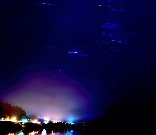 ダム湖に夜景と星の光跡