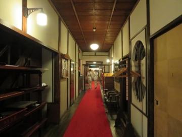 廊下、着物にレトロなカフェエプロンの仲居さん達