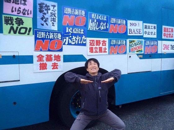 滋賀県から辺野古に押しかけたキム・キガン。警察車両に無断でポスターを貼り、貶めるポーズ。