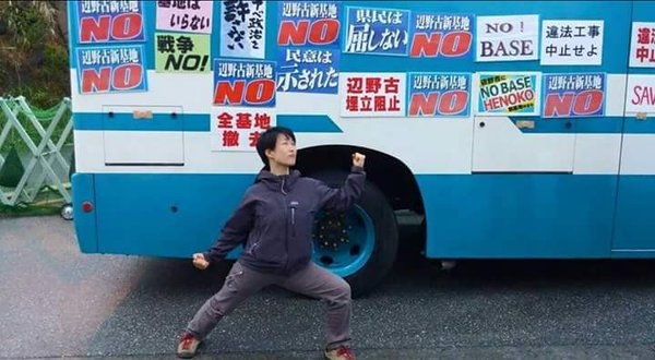 滋賀県から辺野古に押しかけた在日朝鮮人のキム・キガン。警察車両に無断でポスターを貼り、貶めるポーズ。