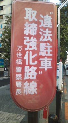 「違法駐車取締強化路線」と万世橋警察署長の名前で示す看板が、すすけて泣いているぞ!