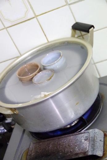 陶器を米のとぎ汁で炊く光景