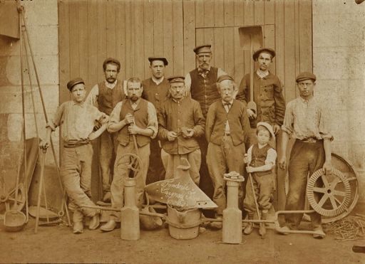 Antique occupational photo of workers with a young helper, tools and gears_512