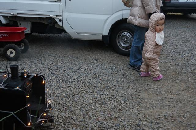 夕焼けが迫る電飾汽車と小さな人間