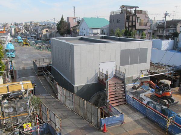 同じ歩道橋から新宿方面を見る。シールドマシンの立坑の上には換気設備の建屋が完成した。奥では緩行線のトンネル建設が続く。