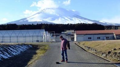 富士山を背景にしたを脱ぎはじめた僕を友人がネオ一眼レフカメラで撮影