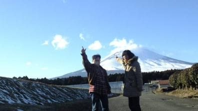 富士山を背景に友人と2人で一眼レフカメラのセルフタイマーで写真撮影