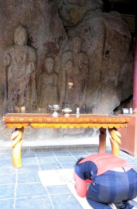 泰安・磨崖三尊仏像に伏して祈る女性