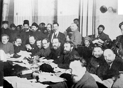 ボリシェヴィキの党員集会 着席の人物は(左端から)、エヌキーゼ、カリーニン、ブハーリン、トムスキー、ラシェヴィッチ、カーメネフ、プレオブラジェンスキー、セレブリャコフ、レーニン、ルイコフ